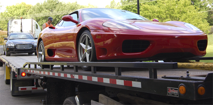 Luxury cars getting towed on a flatbed.